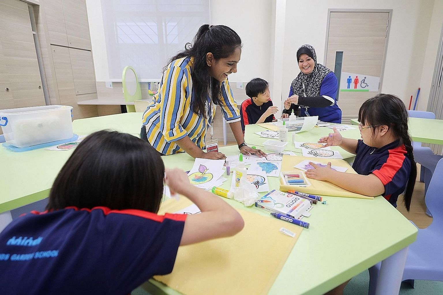 Above: Volunteer Nagakalishwari Ramesh (in stripes) and training officer Nurimah Ghani helping Minds students (from left) Vicky Chew (back to camera), 12, Roy Hong, 17, and Amanda Wang, nine, with their glitter art at Minds Raintree yesterday. Below: