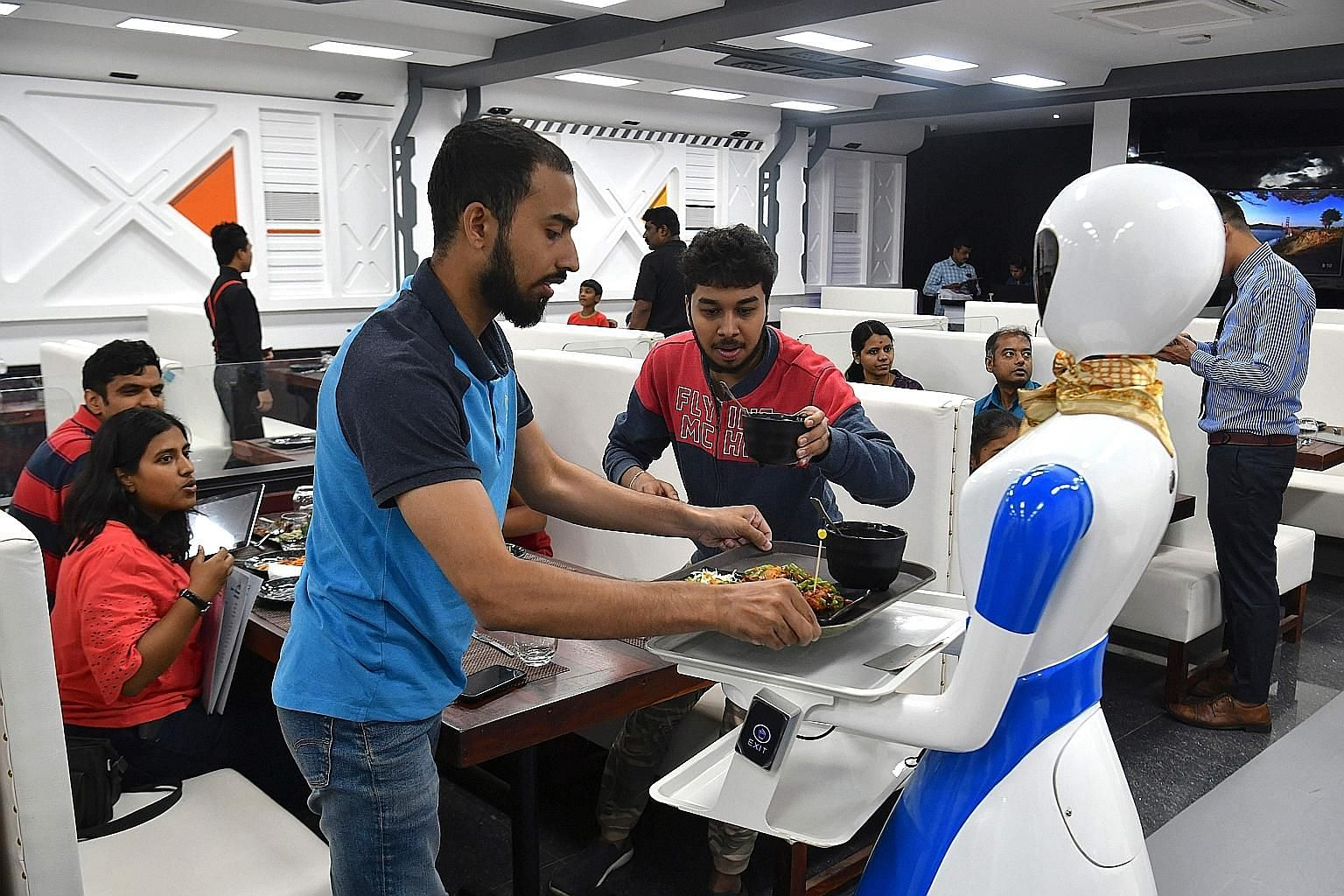 "A service robot delivering food to customers on the opening day of the ""Robot"" restaurant in Bangalore on Aug 17. The restaurant has introduced five robots to interact with and serve food to its customers."