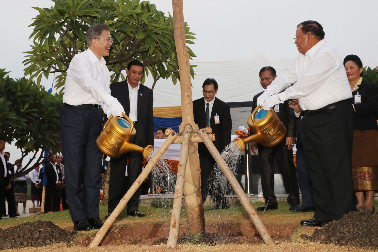 South Korean President Moon Jae-in and Laotian President Bounnhang Vorachith watering a tree after planting it together on the bank of the Mekong River on Thursday. Mr Moon was in Laos during his six-day trip to three South-east Asian countries. PHOT