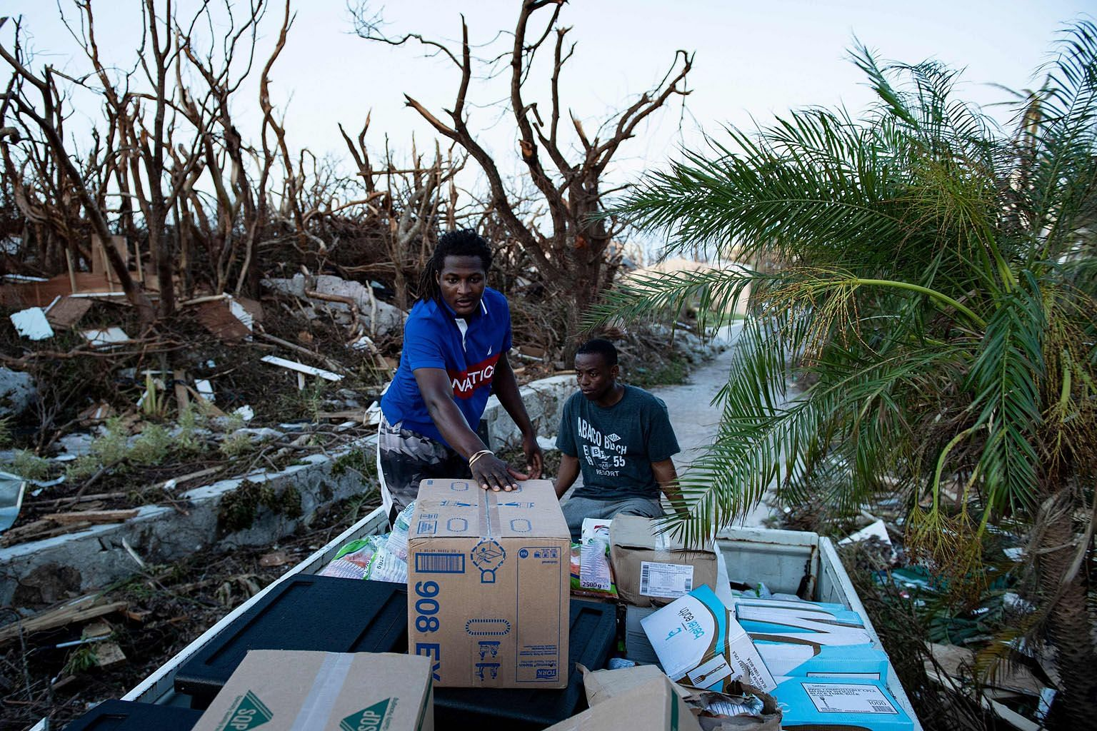 Above: Volunteers with World Central Kitchen transporting food supplies for survivors of Hurricane Dorian on Thursday in Marsh Harbour, Great Abaco, the Bahamas. Below: Residents of a caravan park in Emerald Isle, North Carolina, surveying the damage