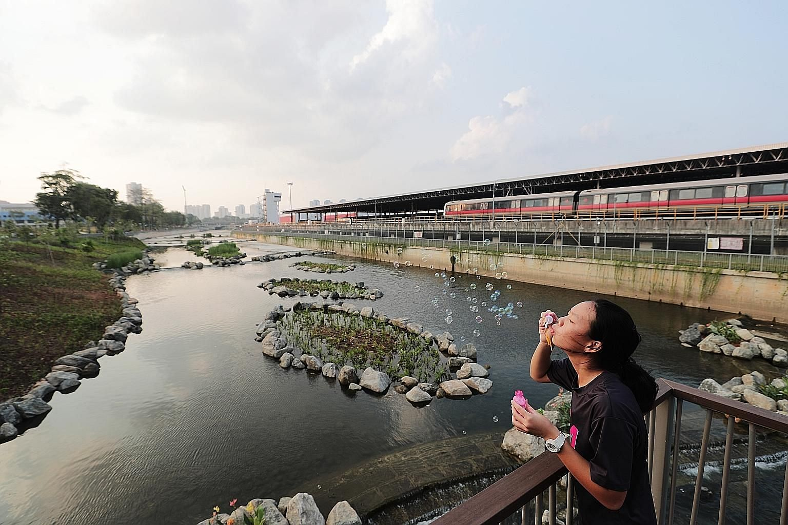 Bishan resident Sharon Quek, 14, having fun at the upgraded stretch of the Kallang River yesterday. Features to beautify the area include a naturalised slope, small islands with plants, and water cascades that help the water to flow from a higher ele