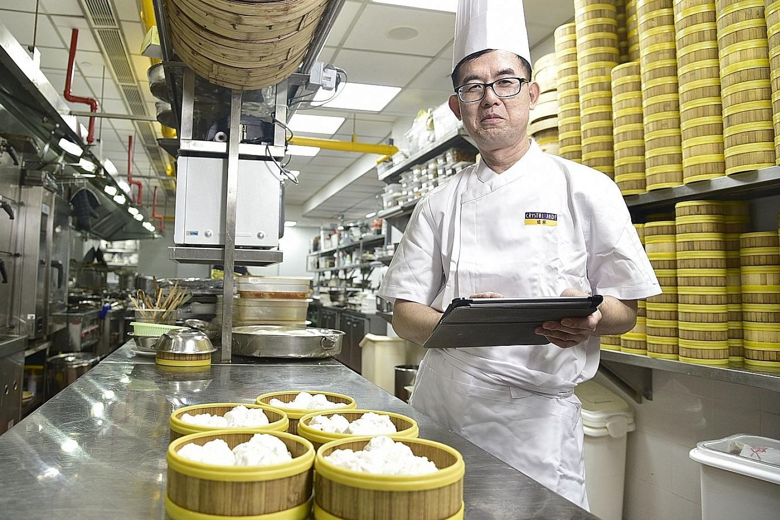 Besides machines that help make pastries, chef Shum Chun Yi also appreciates new electronic processes such as using a tablet computer to order inventory items directly from suppliers. ST PHOTO: DESMOND WEE