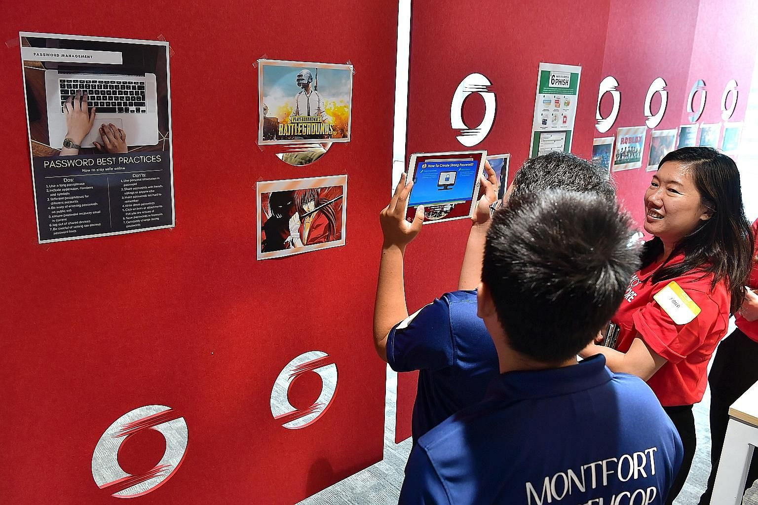 """Participants at the coding and cyber-security workshop at Bank of Singapore's office in Raffles Place yesterday. For the AR activity, students used an app on a tablet to """"scan"""" posters of video games put up on a wall, before watching a video and answ"""