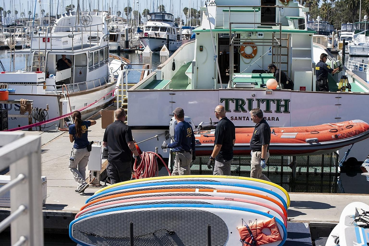 The authorities at the Truth, a diving boat owned by Truth Aquatics, the firm involved in last week's boat fire tragedy, at the Santa Barbara Harbour in California on Sunday. The Santa Barbara County Sheriff said the search warrants that have been se