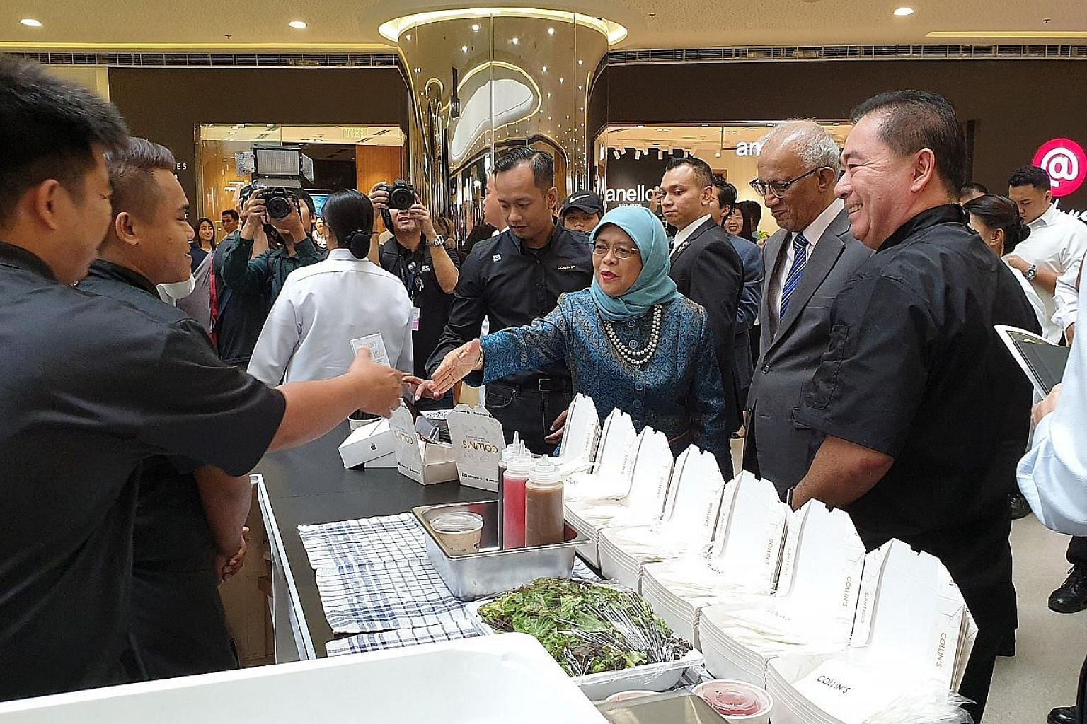 President Halimah Yacob interacting with staff from food and beverage brand Collin's at Singaporium, a consumer and lifestyle pop-up in Manila. She was accompanied by her husband, Mr Mohamed Abdullah Alhabshee (second from right). ST PHOTO: SUE-ANN T