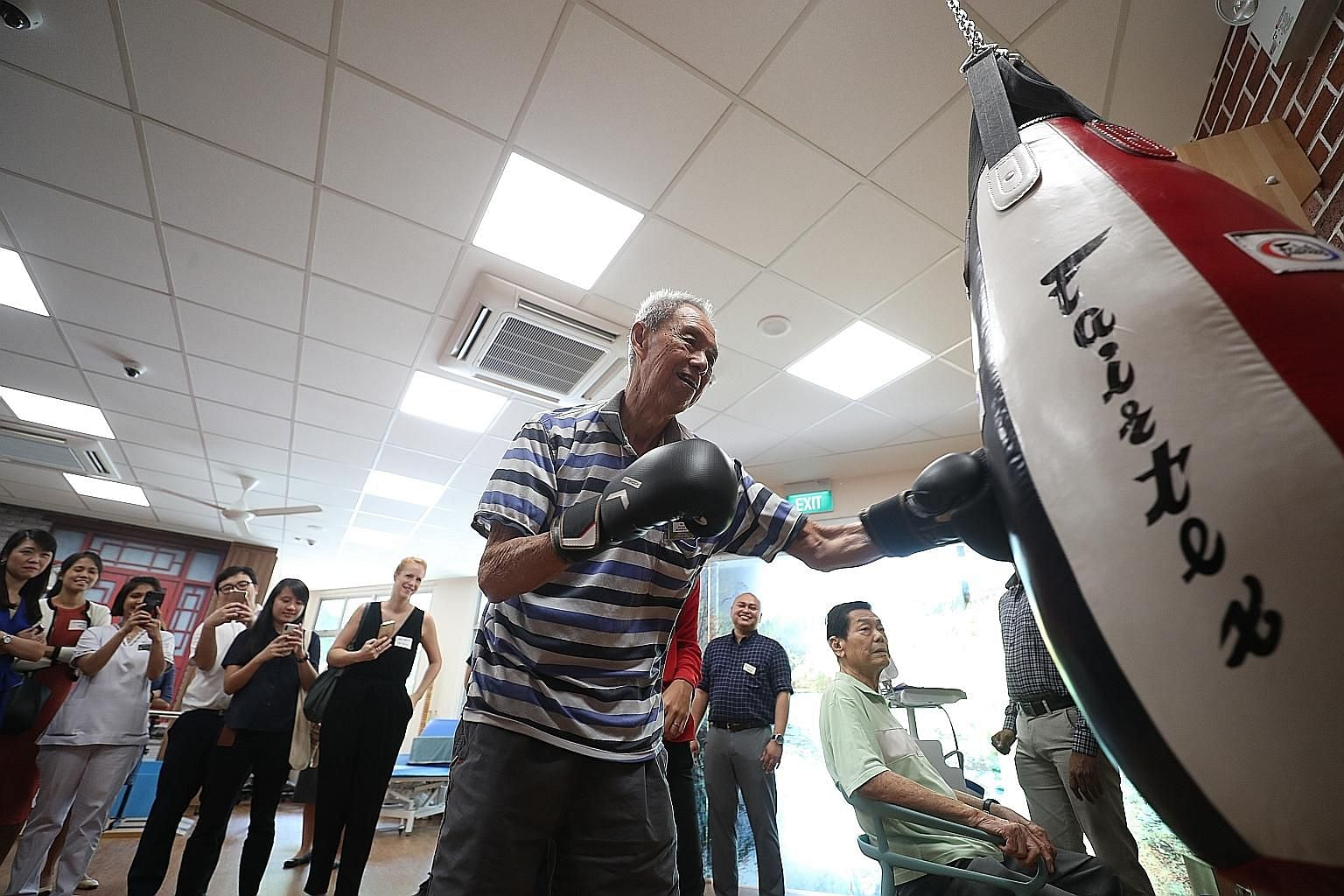 Mr Ho Ah Eng throwing punches at a punching bag at the Telok Blangah Senior Care Centre's rehab gym. Mr Ho, 81, who has an unsteady gait and lower-limb injury, says the weekly boxing classes at the centre have helped improve his balance and strength.