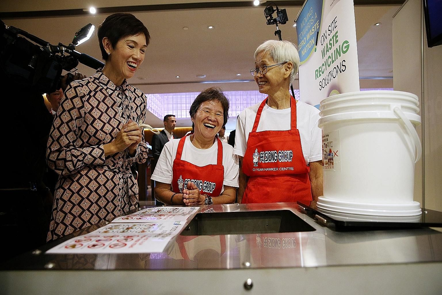 (From left) Manpower Minister Josephine Teo chatting with Madam Ong Poh Kee, 57, and Madam Chua Cher Kee, 75, both cleaning ambassadors at Fei Siong, about an eco-digester that turns food waste into water and carbon dioxide and helps lighten cleaning