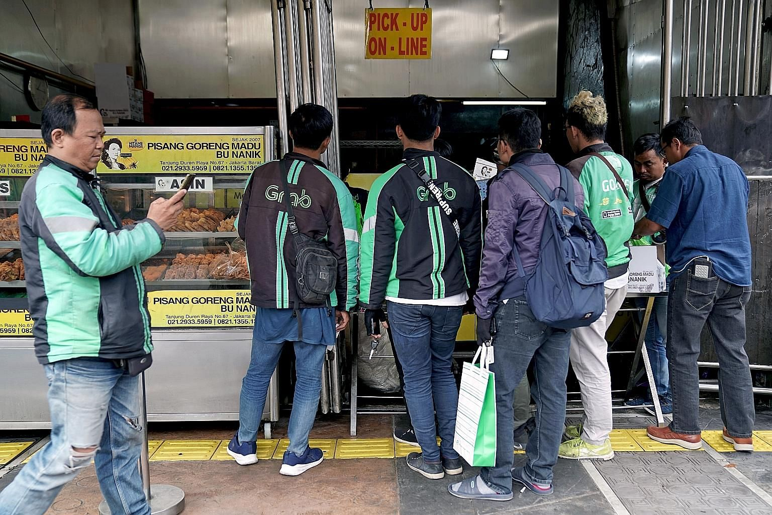 GrabFood drivers queueing up to collect orders at an eatery in Jakarta in July. Grab and Gojek are the top two start-up brands in South-east Asia, and they compete in areas such as financial services, e-commerce, ride hailing and food delivery. PHOTO