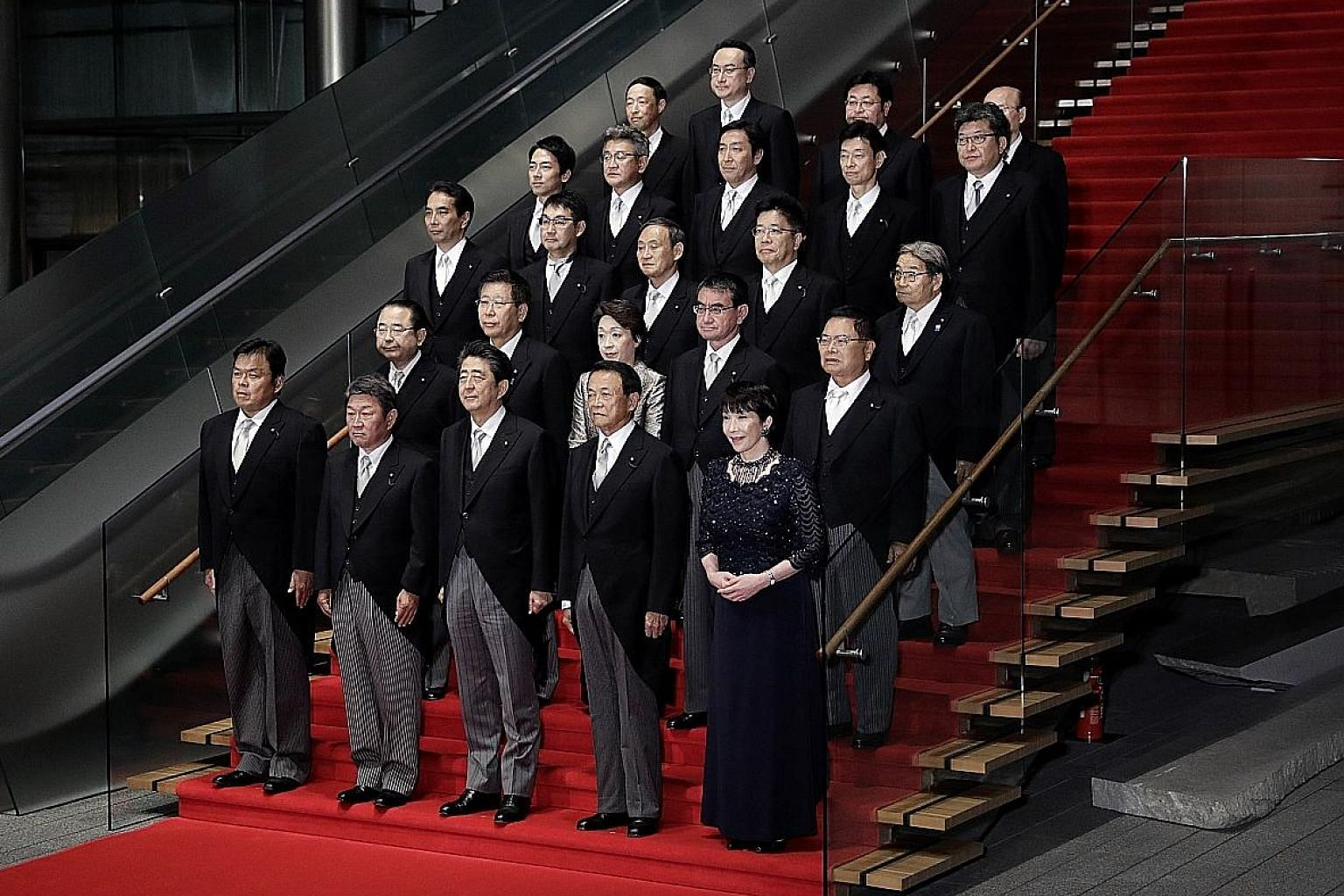 Japanese Prime Minister Shinzo Abe (front row, centre) with members of his new Cabinet in Tokyo on Wednesday. Experts see Mr Abe as attempting to revise, for the first time in history, Japan's pacifist charter by surrounding himself with those who ar