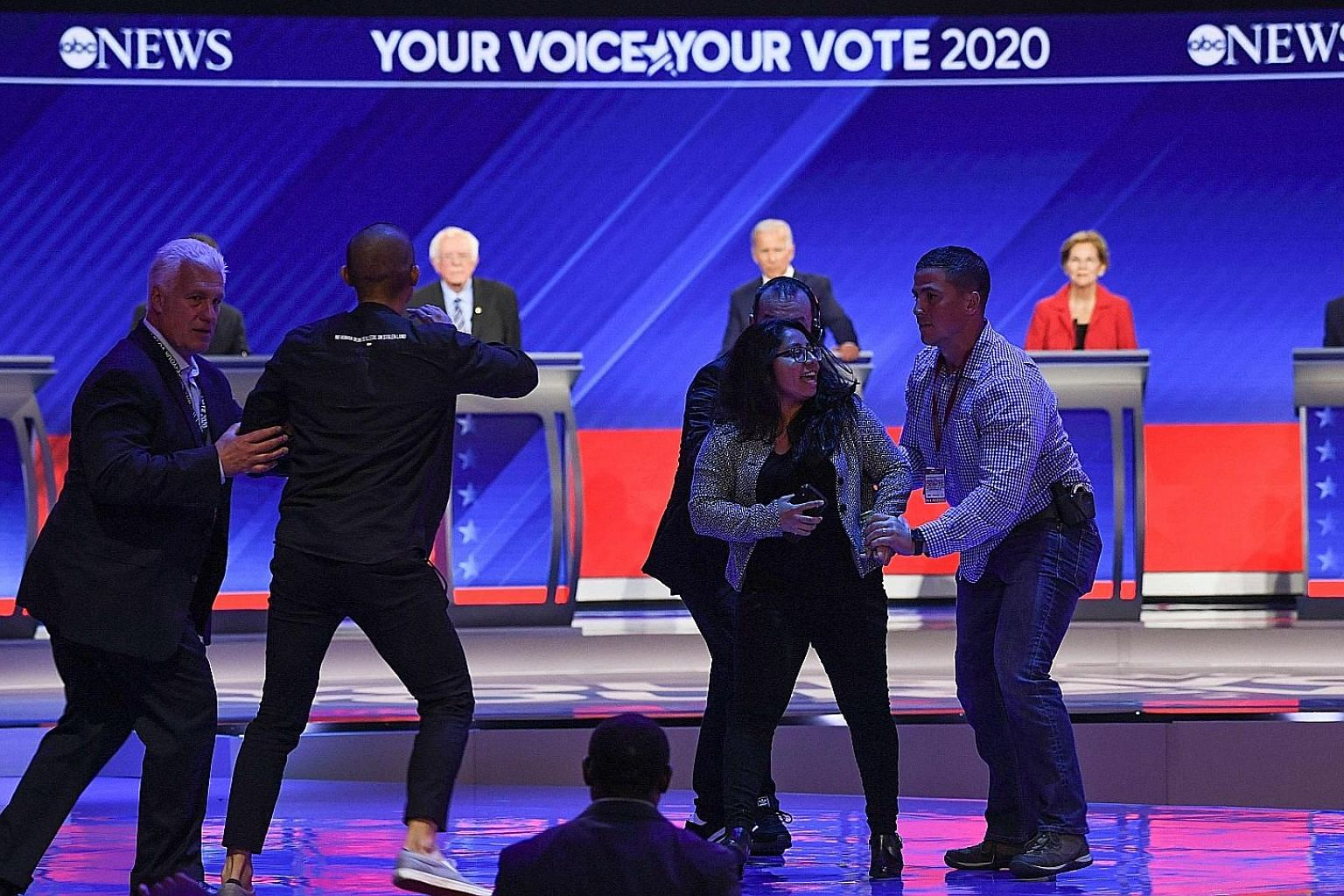 Protesters being escorted off the stage at the third Democratic primary debate in Houston, Texas, on Thursday, as (from left) Senator Bernie Sanders, former vice-president Joe Biden and Senator Elizabeth Warren look on. Ten presidential hopefuls part