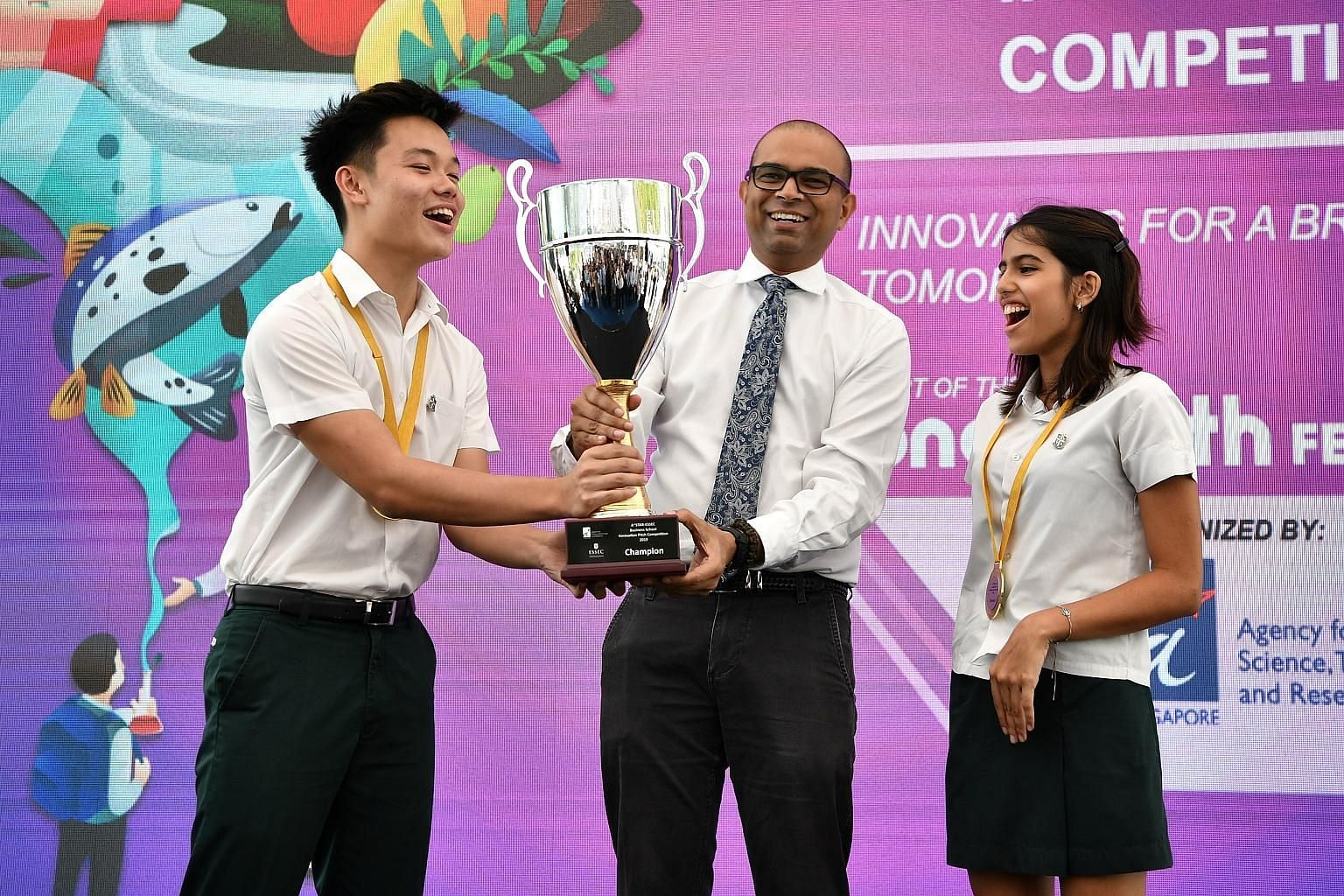 Dr Janil Puthucheary, Senior Minister of State for Transport and Communications and Information, presenting the trophy yesterday to Mr Kyle Tan and Ms Tara Kripalani from the St Joseph's Institution International team which clinched first place in th
