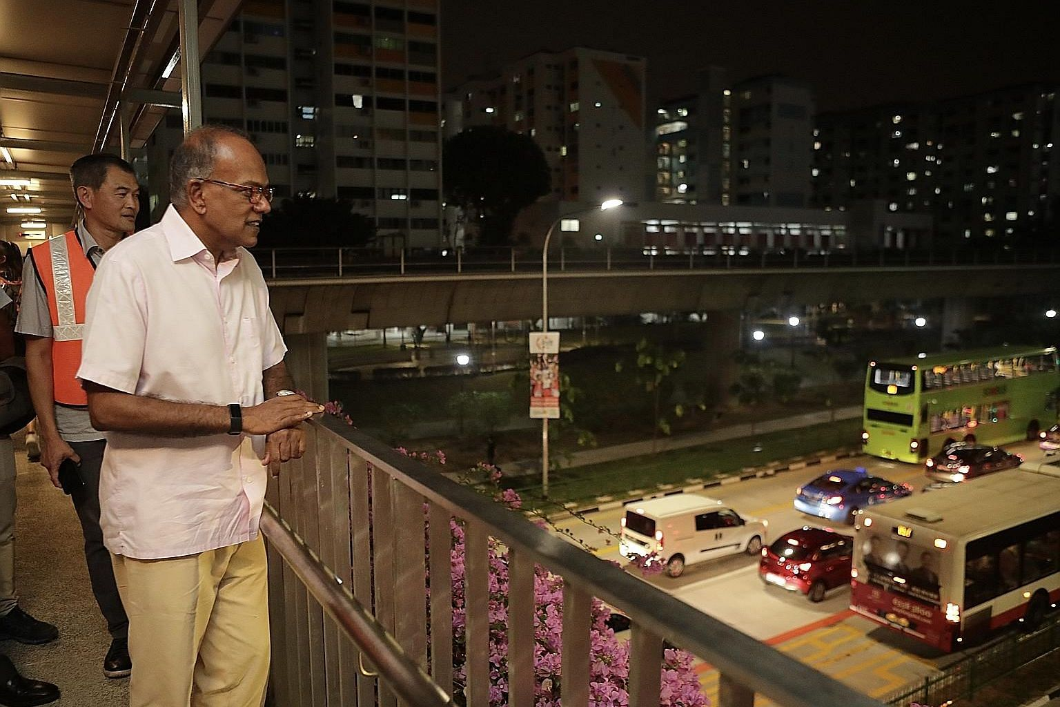 Law and Home Affairs Minister K. Shanmugam observing road conditions from an overhead bridge in Yishun Avenue 2 last night. Mr Shanmugam, seen here with Mr Lee Yong Heng, general manager of Mandai zone at SMRT Buses, was visiting the area around the