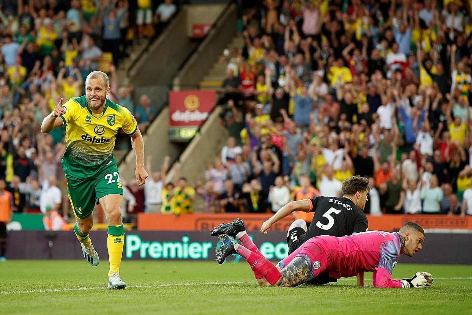 Norwich City's Teemu Pukki celebrating after scoring his team's third goal on Saturday, leaving the crestfallen City defender John Stones and goalkeeper Ederson looking for answers.