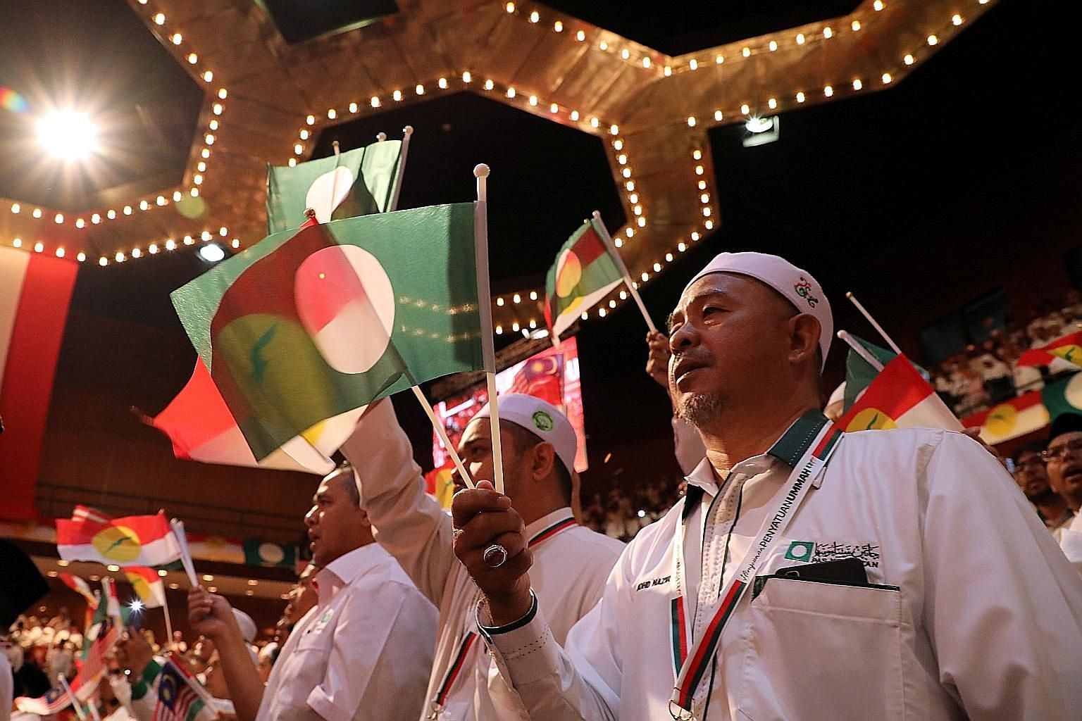 """Members of opposition parties Umno and Parti Islam SeMalaysia (PAS) at the Muslim Unity Gathering in Umno's PWTC headquarters in Kuala Lumpur on Saturday. PAS president Hadi Awang described the gathering as a """"family affair"""", although party members a"""
