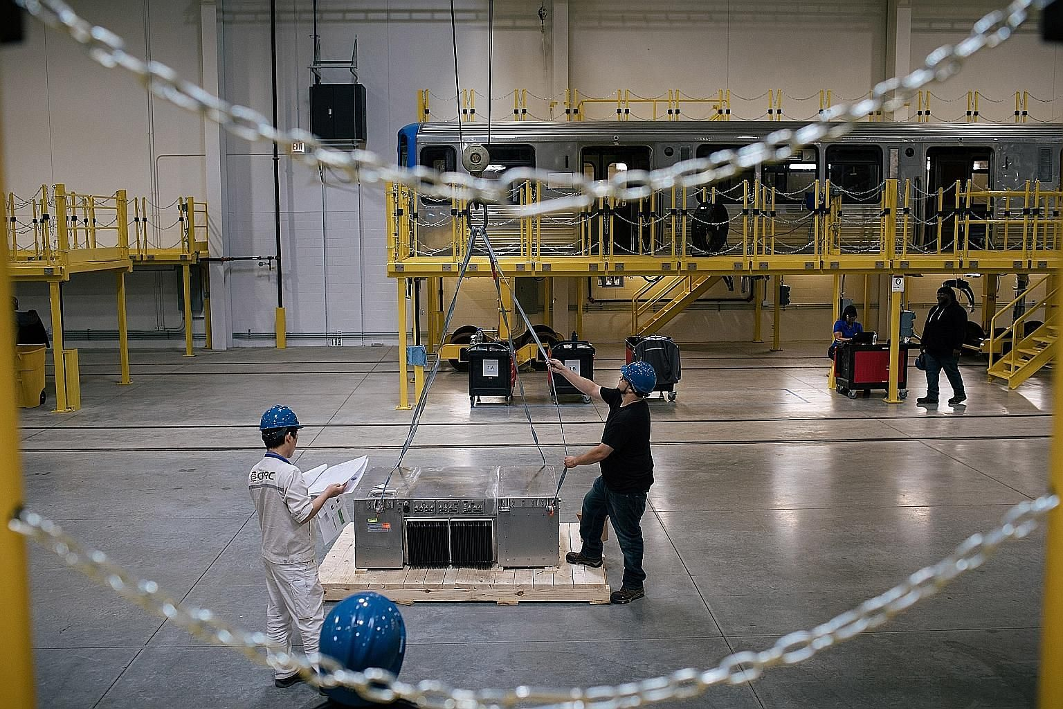Workers moving an auxiliary power supply at CRRC Corp's Chicago plant last month. The Chinese train maker completed the US$100 million (S$137 million) facility this year in the hope of winning contracts to build subway cars and other passenger trains