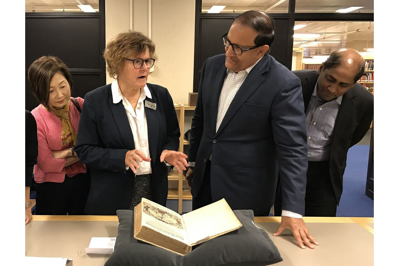 At the National Library of the Netherlands, Dr Marieke van Delft shows Minister for Communications and Information S. Iswaran the Itinerario, an account of the East Indies containing hand-coloured maps and illustrations by Jan H. van Linschoten. Also on t