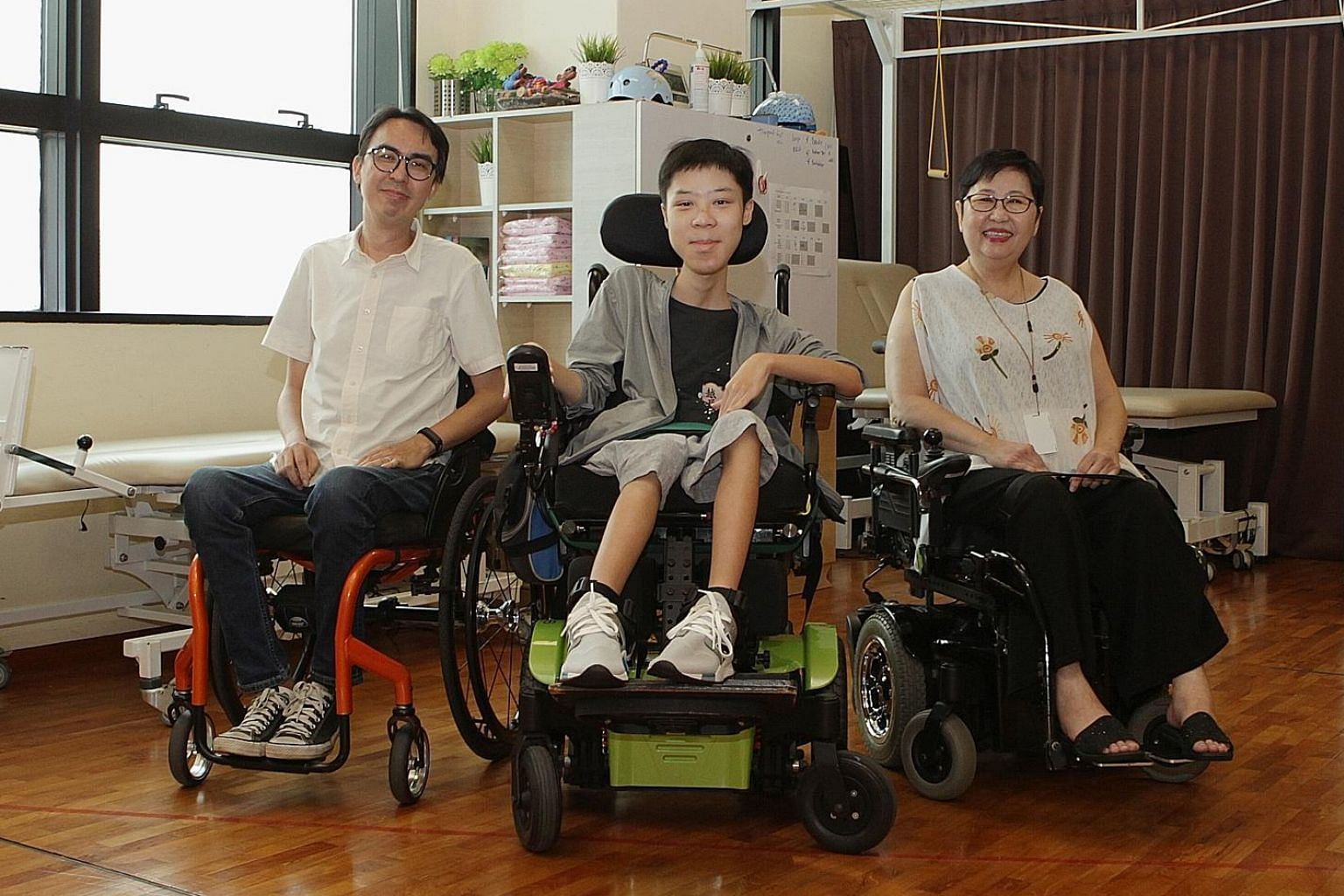 From left: Mr Alvin Seah, 39, Mr Desmond Lam, 19, and Ms Sherena Loh, 59, who all have a form of muscular dystrophy, at the Muscular Dystrophy Association (Singapore). The centre needs more funds to continue running and expanding its programmes, whic
