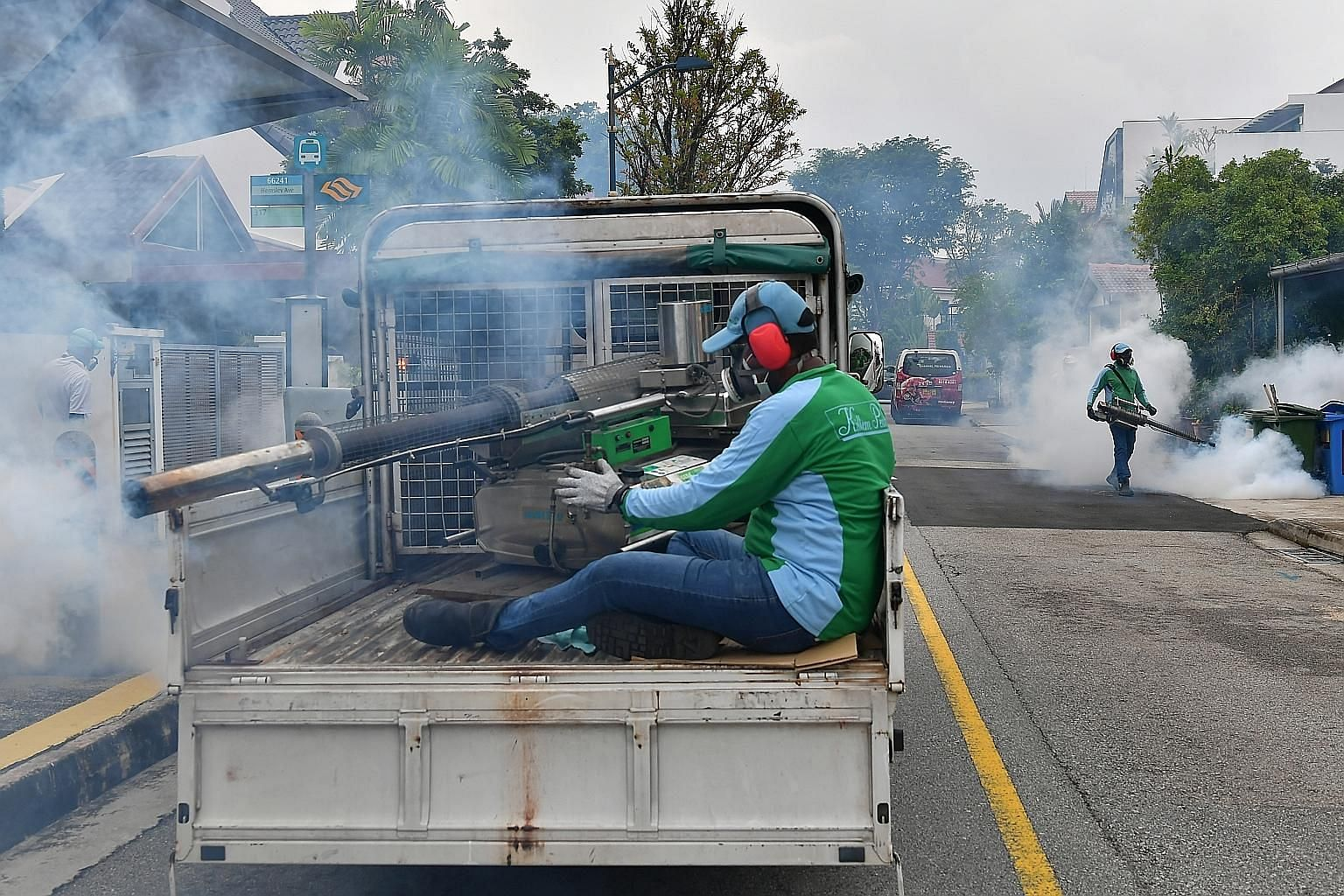 Pest control and National Environment Agency officers conducting fogging in Hemsley Avenue in Serangoon Gardens on Sunday. ST PHOTO: NG SOR LUAN