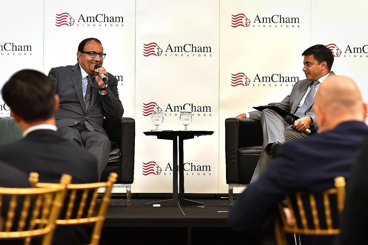 Mr S. Iswaran (far left), with dialogue moderator Kunal Chatterjee, Visa's country manager for Singapore and Brunei, speaking at the American Chamber of Commerce luncheon yesterday. ST PHOTO: NG SOR LUAN
