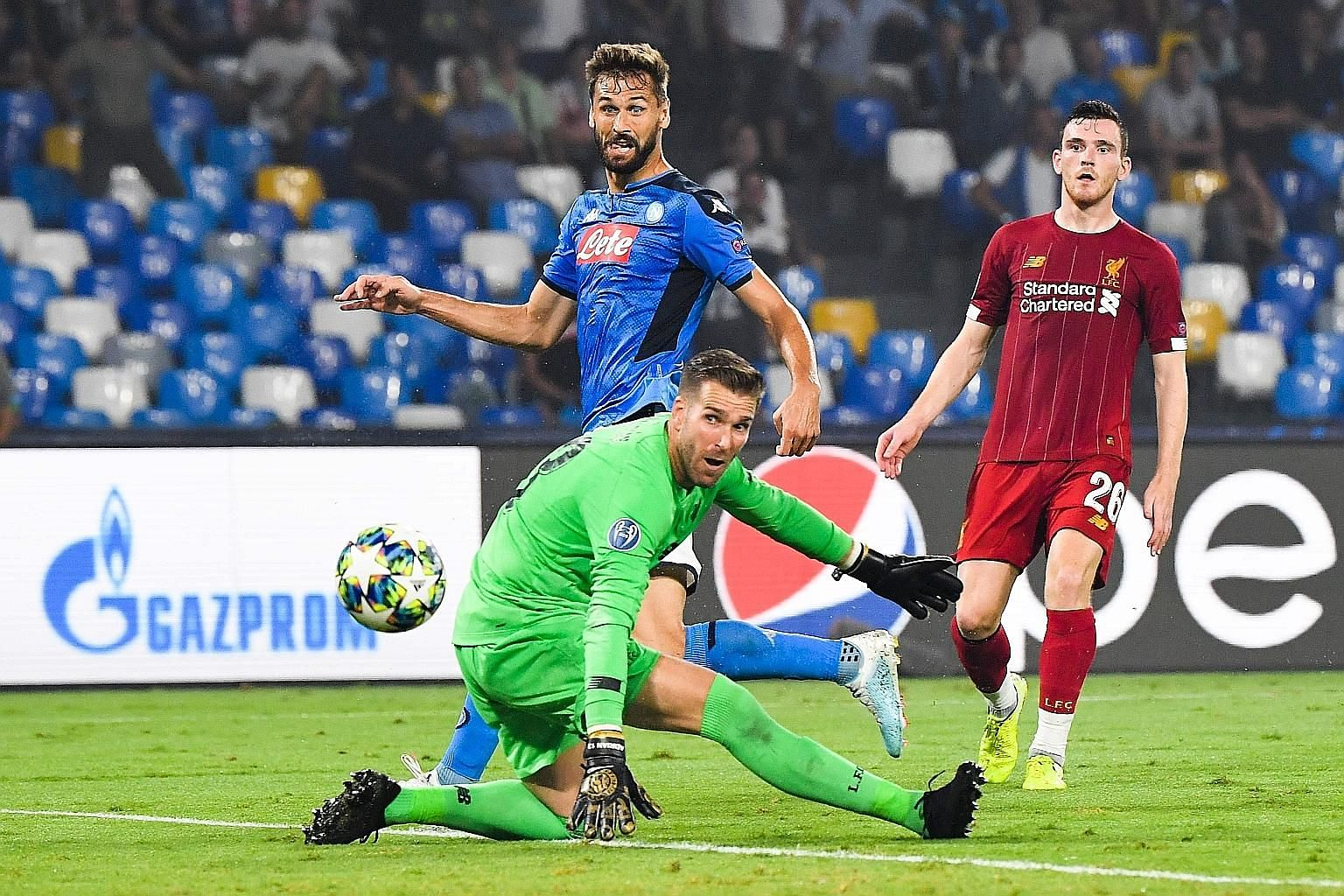 Napoli forward Fernando Llorente (in blue) scoring past Liverpool goalkeeper Adrian during their Champions League clash on Tuesday night. Napoli won the match 2-0 thanks to a penalty and a mistake by Virgil van Dijk which Llorente took advantage of.