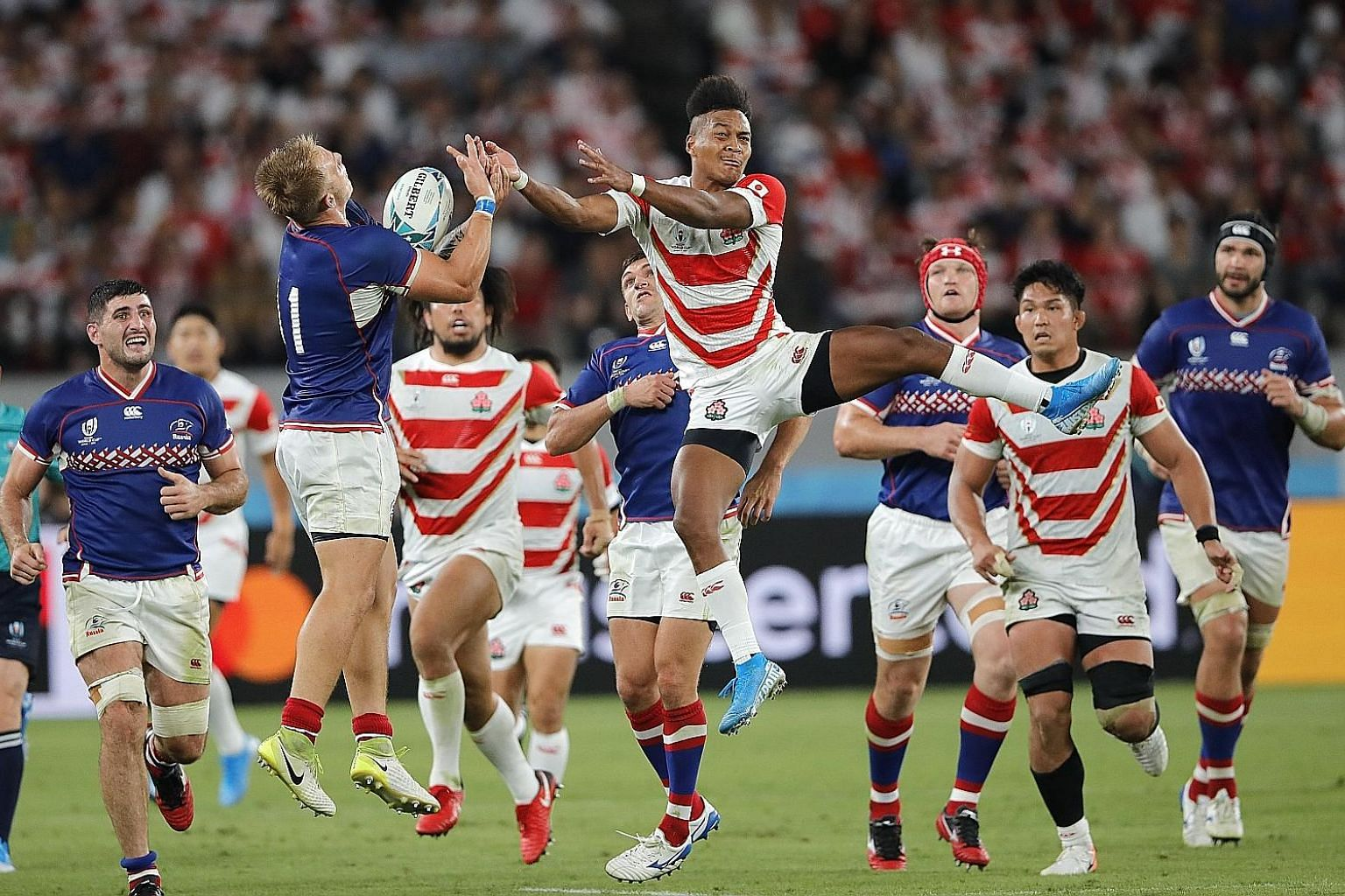 Japan's Kotaro Matsushima (centre) jumping to claim the ball in the Rugby World Cup game against Russia yesterday at Tokyo Stadium. PHOTO: ASSOCIATED PRESS