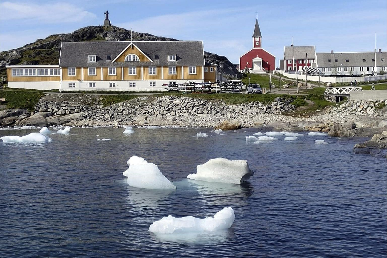 Pieces of ice floating in the water off the shore in Nuuk, capital of Greenland. Record heat this year triggered extreme melting in the country. Scientists estimate that by the end of the summer, enough ice will have melted or calved off its ice shee