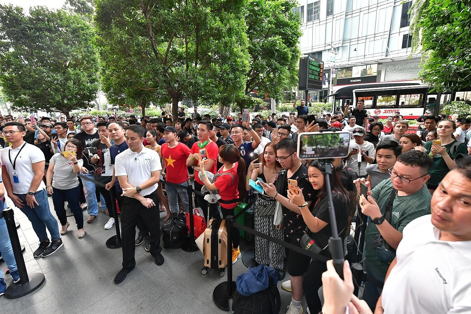 Mr Ryan Le, 28, from Ho Chi Minh, with iPhones bought by his compatriots at the Apple store in Orchard. He himself bought two iPhones. A crowd queueing outside Apple's Orchard Road flagship store before the launch of the latest iPhone 11 series yeste