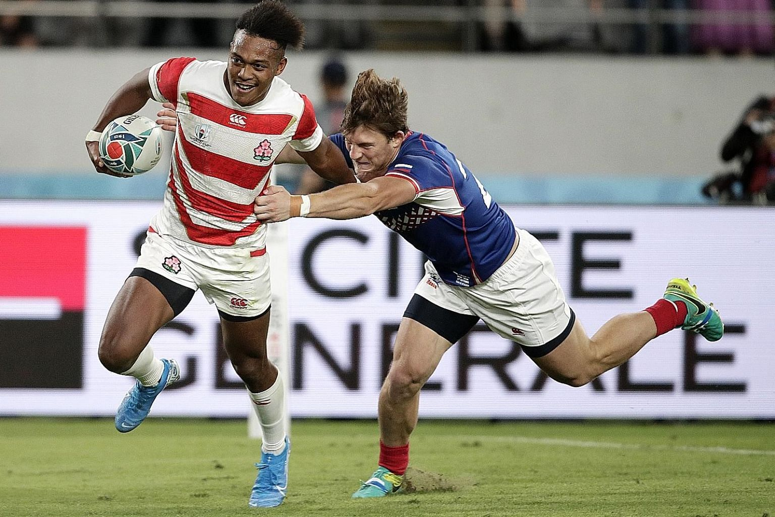 Japan's Kotaro Matsushima fending off Russia's Vladislav Sozonov to score his third try in the Rugby World Cup Pool A game at Tokyo Stadium last night. The utility back is the first player to score three tries in a World Cup opener.