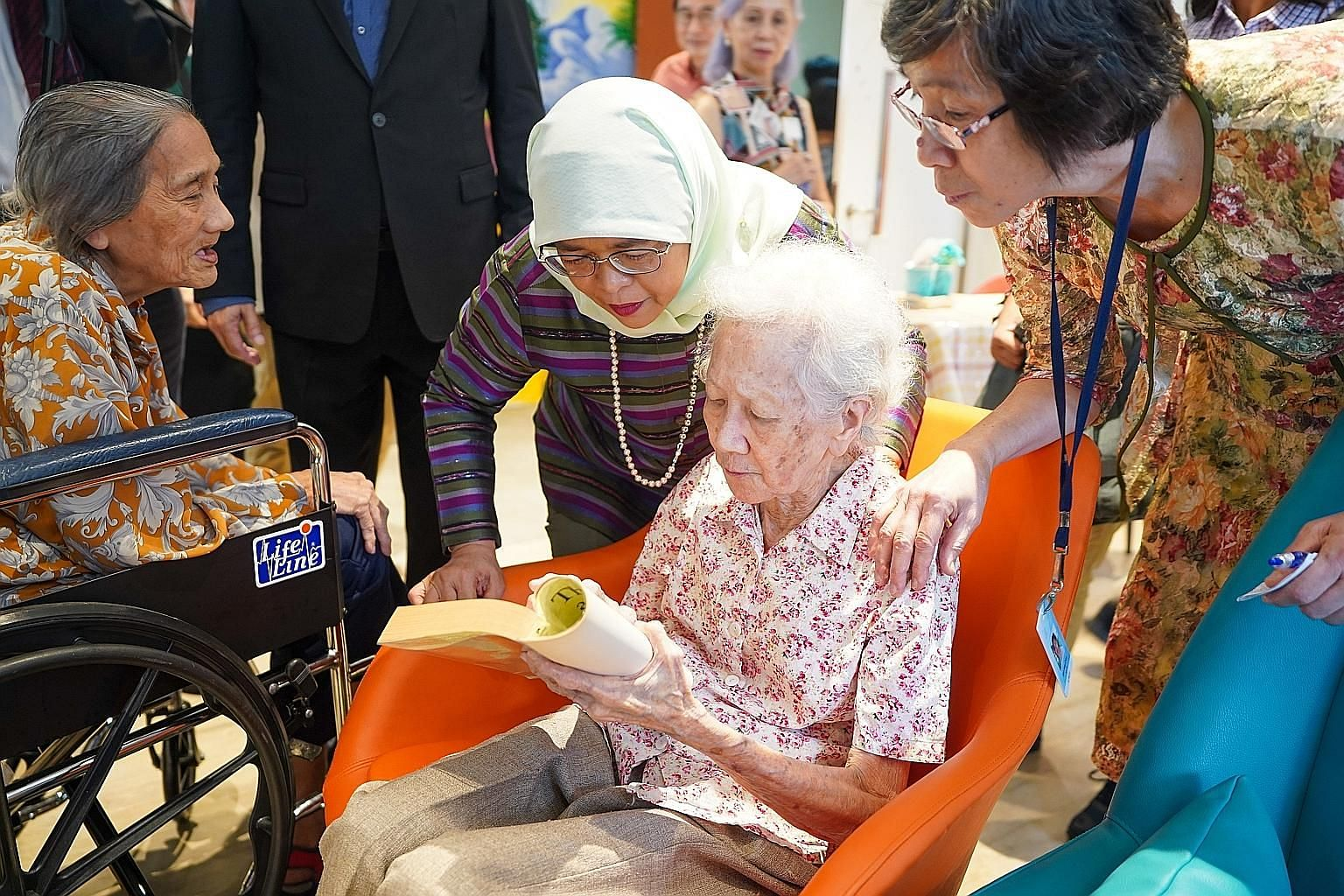 President Halimah Yacob checking out a book on dementia held up by Madam Mary Sng, a 92-year-old resident of Apex Harmony Lodge in Pasir Ris. Madam Halimah yesterday toured the premises of the long-term residential care facility for people with demen
