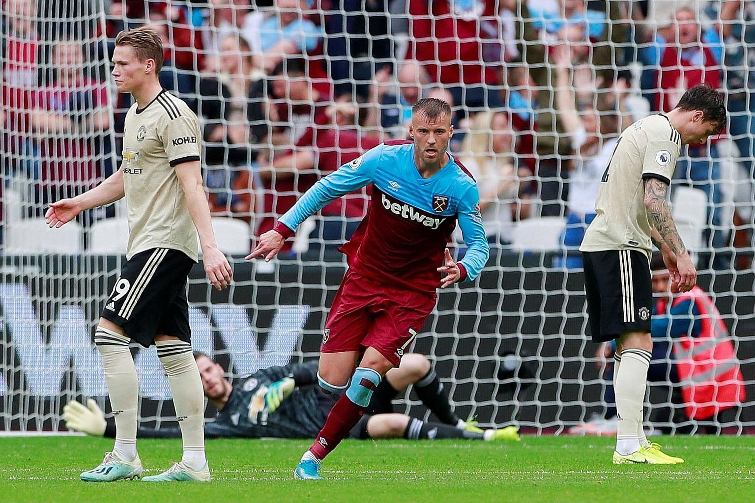 West Ham's Andriy Yarmolenko wheels away to celebrate scoring their first goal against Manchester United as Scott McTominay (left) and Tobias Lindelof appear dejected.