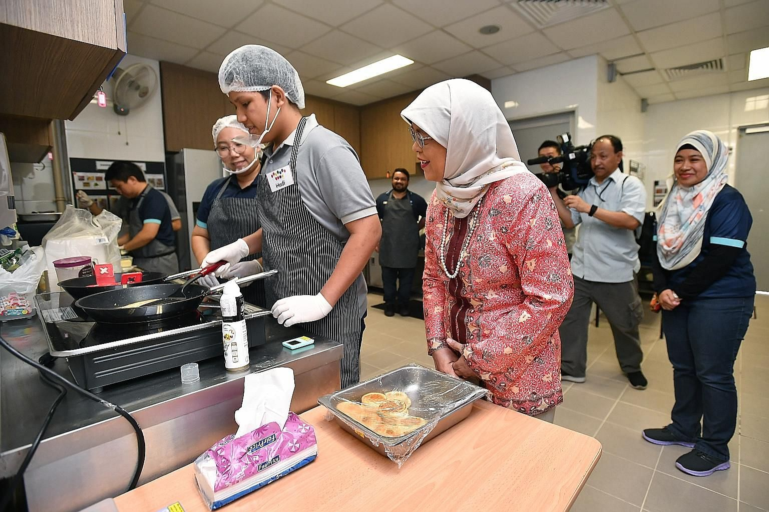 President Halimah Yacob watching Hadi Ukasyah Noor Asahar, 14, prepare food in the kitchen of Colours Cafe at St Andrew's Autism School yesterday. The in-house school cafe is run by students capable of work, so that they can develop skills and work h