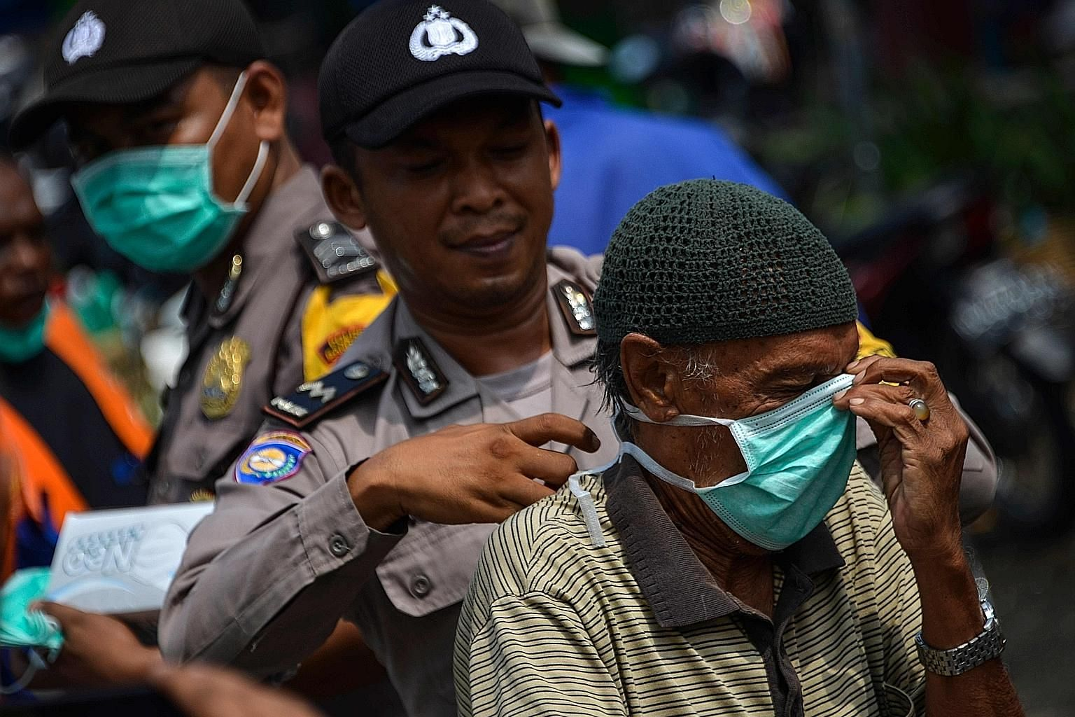 A police officer helping a motorist put on a face mask in Banda Aceh, in Sumatra, yesterday. There were 3,150 hot spots across Indonesia on Monday. But by Tuesday, the number had dropped sharply to 1,982 before slipping to 1,744 yesterday, Indonesia'
