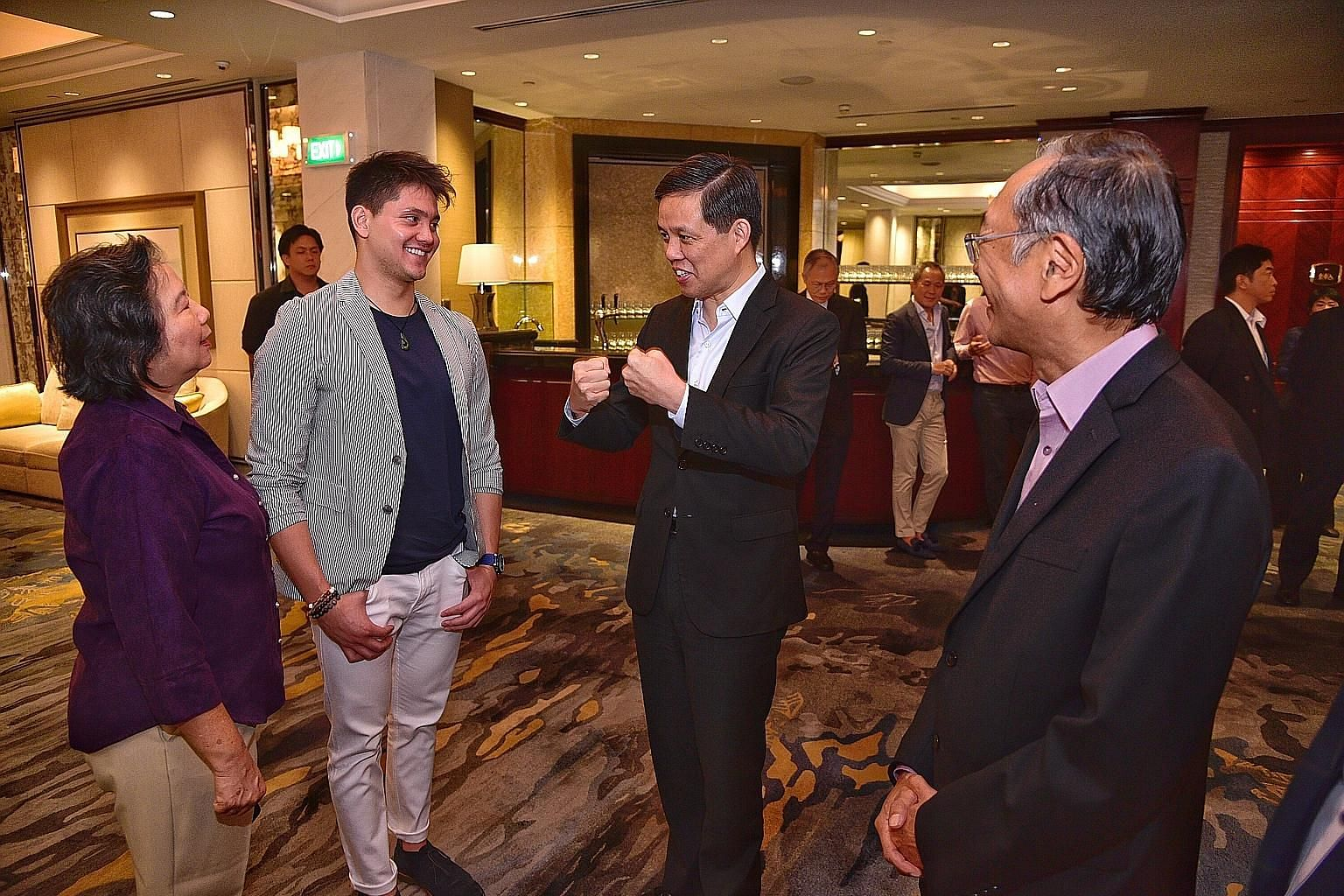 Minister for Trade and Industry Chan Chun Sing, the guest of honour at the Singapore Swimming Association's fund-raising dinner, speaking to Olympic gold medallist Joseph Schooling, his mother May and SSA president Lee Kok Choy. ST DESMOND WEE