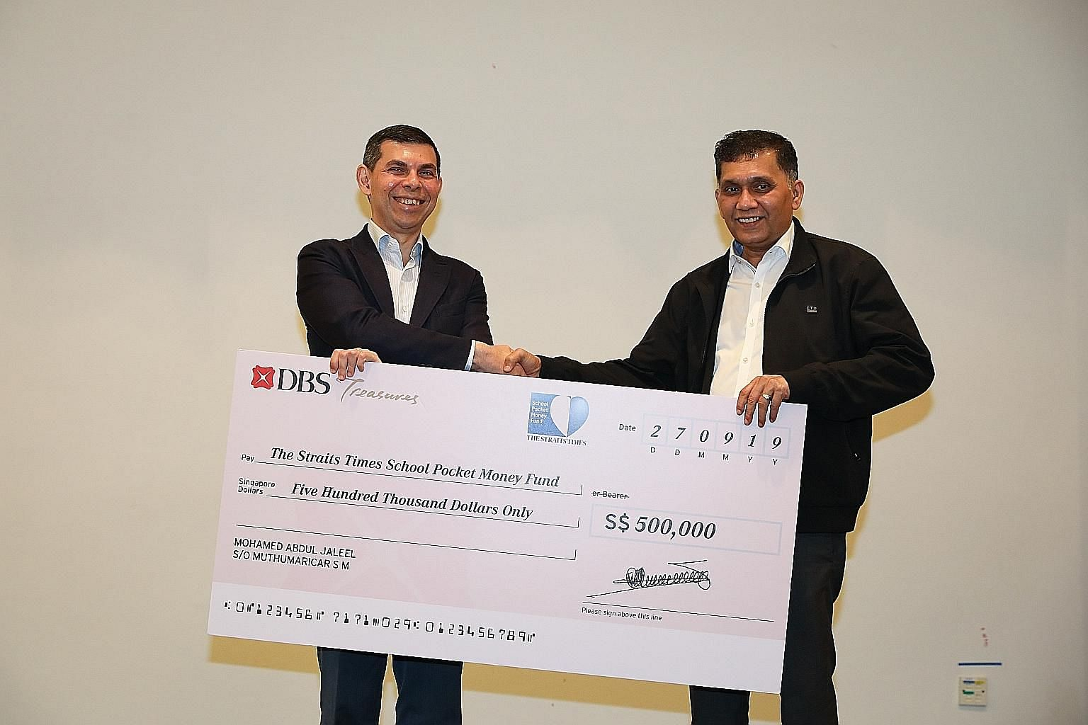 ST School Pocket Money Fund chairman Warren Fernandez (left) receiving a donation of $500,000 to the fund from Mini Environment Service Group founder and chief executive Mohamed Abdul Jaleel yesterday. Mr Jaleel, a long-time supporter of the fund, ha