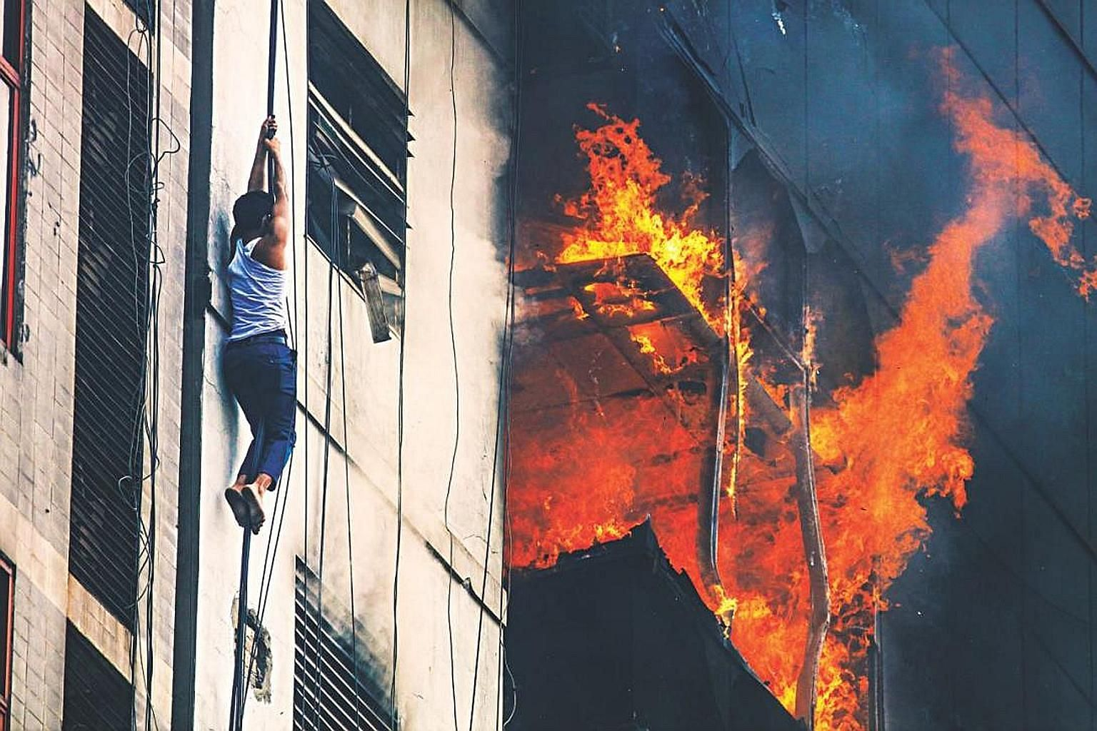 A man trying to escape a fire at FR Tower in Dhaka on March 28 - 26 people died and about 100 were hurt. Fires are not uncommon in densely populated Bangladesh, owing to lax safety regulations and poor building conditions.