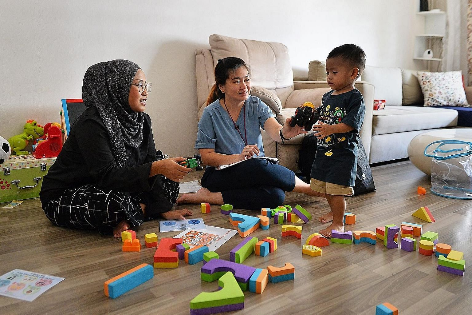 KidStart home visitor Lee Wei Qi, 32, interacting with 19-month-old Ae'dan Raphael. She has helped his mother, Ms Calista Azman, 34, by sharing parenting tips and strategies for her son's development. One feature of KidStart is that support and advic