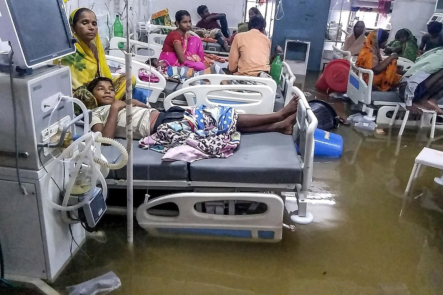 Patients and their relatives waiting out the floods at the waterlogged Nalanda Medical College and Hospital in Patna, in India's north-eastern state of Bihar, yesterday.