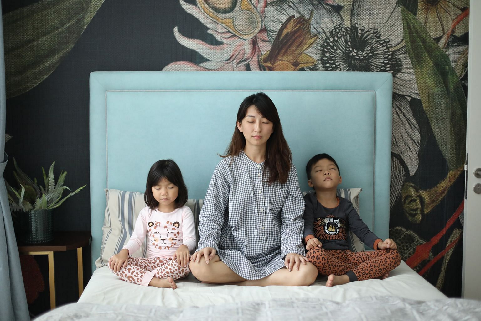 Ms Liang May practising meditation with her children Jing Faye and Ewan before sleep time.