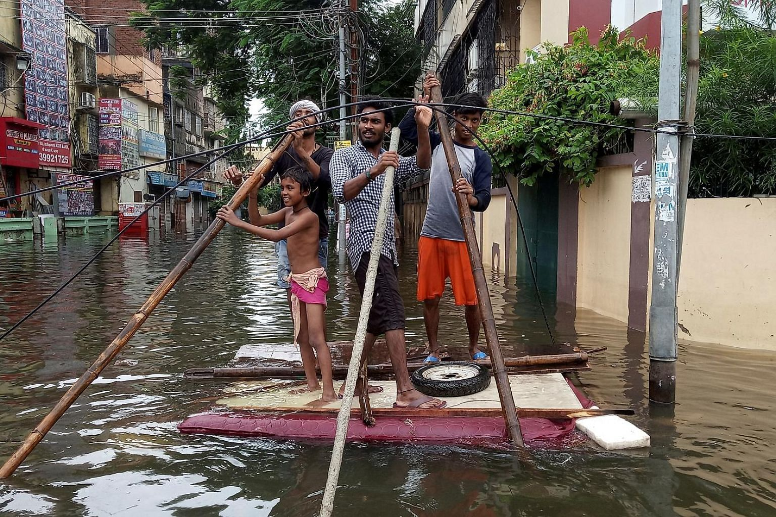 People using a makeshift raft in a flooded neighbourhood of Patna in the eastern state of Bihar yesterday. Heavy rain has killed at least 113 people in India's Uttar Pradesh and Bihar states over the past three days, officials said yesterday as flood