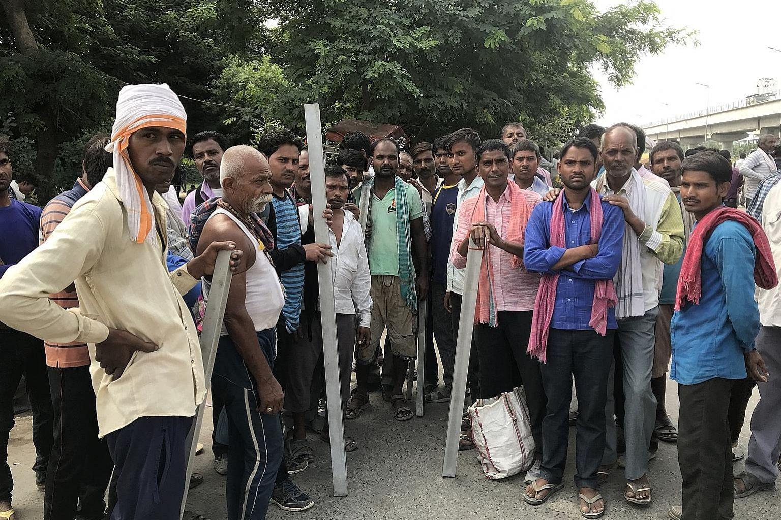Daily-wage labourers and construction workers on the outskirts of New Delhi jostling for jobs earlier last month with a recruiter (in red). Confidence in the Indian economy is giving way to uncertainty as growth in the labour-intensive manufacturing