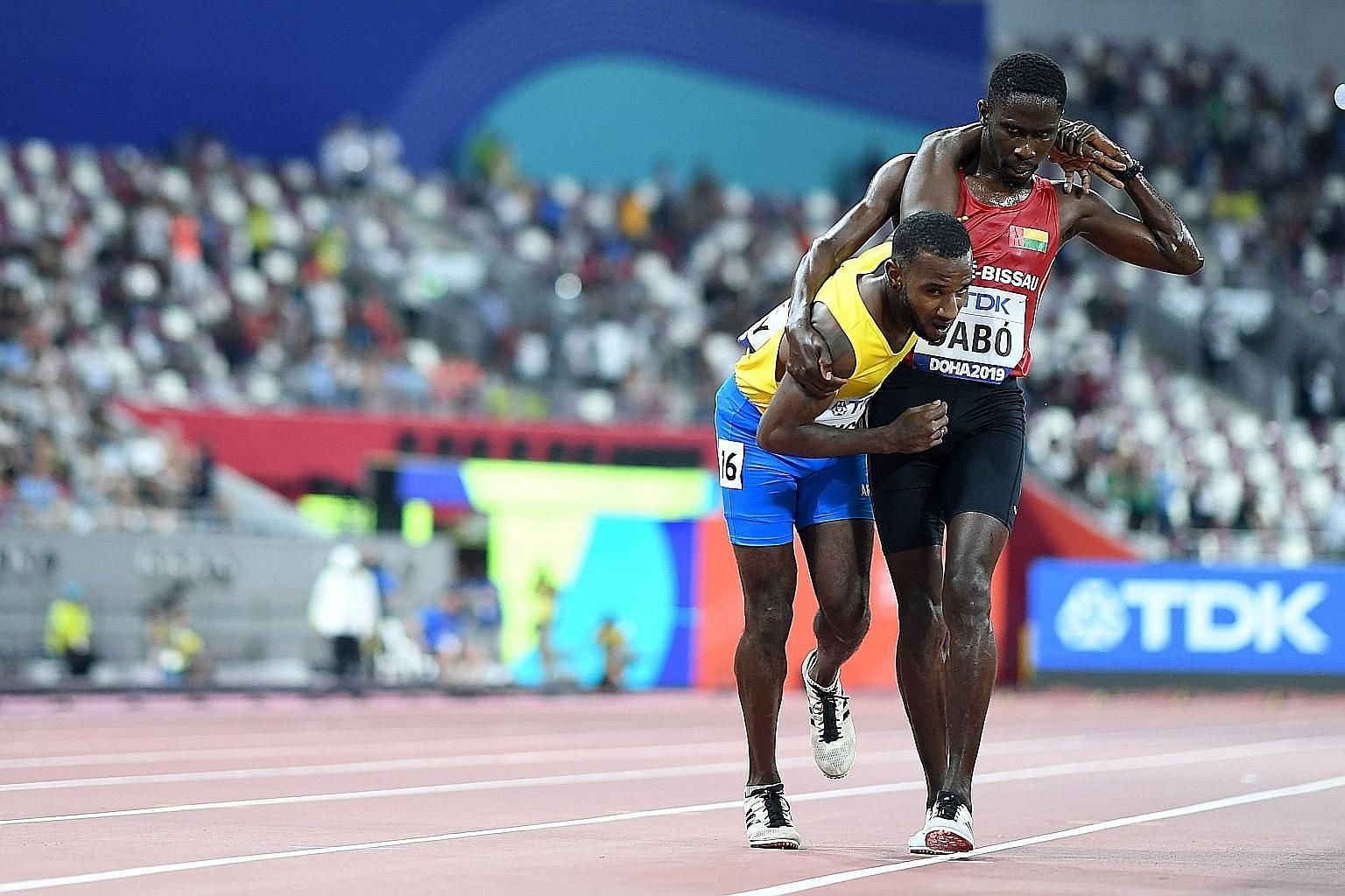 Guinea-Bissau's Braima Suncar Dabo helping Aruba's Jonathan Busby to the finish line in the men's 5,000m heats at the world athletics championships in Doha last Friday. Dabo clocked 18min 10.87sec and did not progress while his heat-affected rival wa