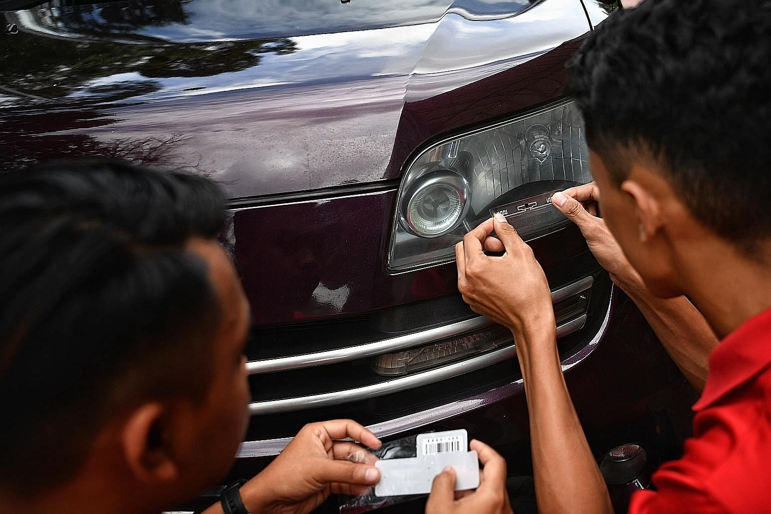 A radio frequency identification tag for Malaysia's Vehicle Entry Permit scheme being placed on the headlamp of a car in Johor Baru in July. The scheme is meant to cover foreign-registered cars entering Malaysia from Singapore.