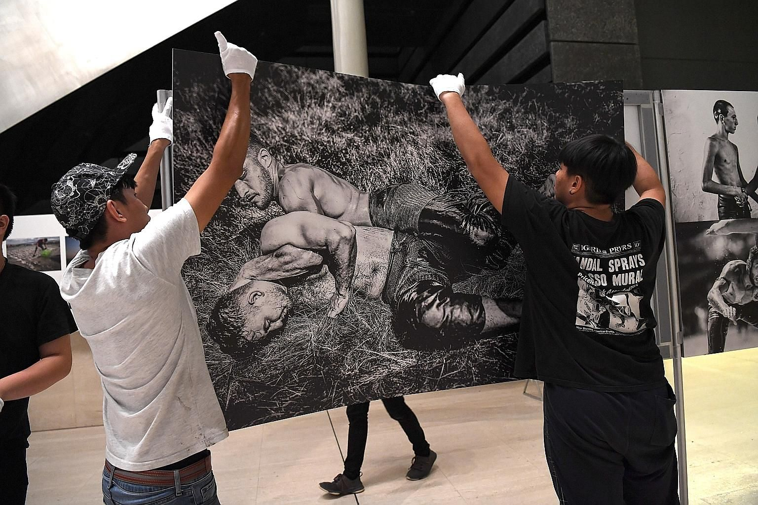 "Assistant event producer Jonathan Shi (far left), 33, and part-time employee Jamus Tan, 18, putting up a winning image that is part of a visual story titled ""Kirkpinar Oil Wrestling Festival"" by photographer Elif Ozturk at the National Museum of Sing"