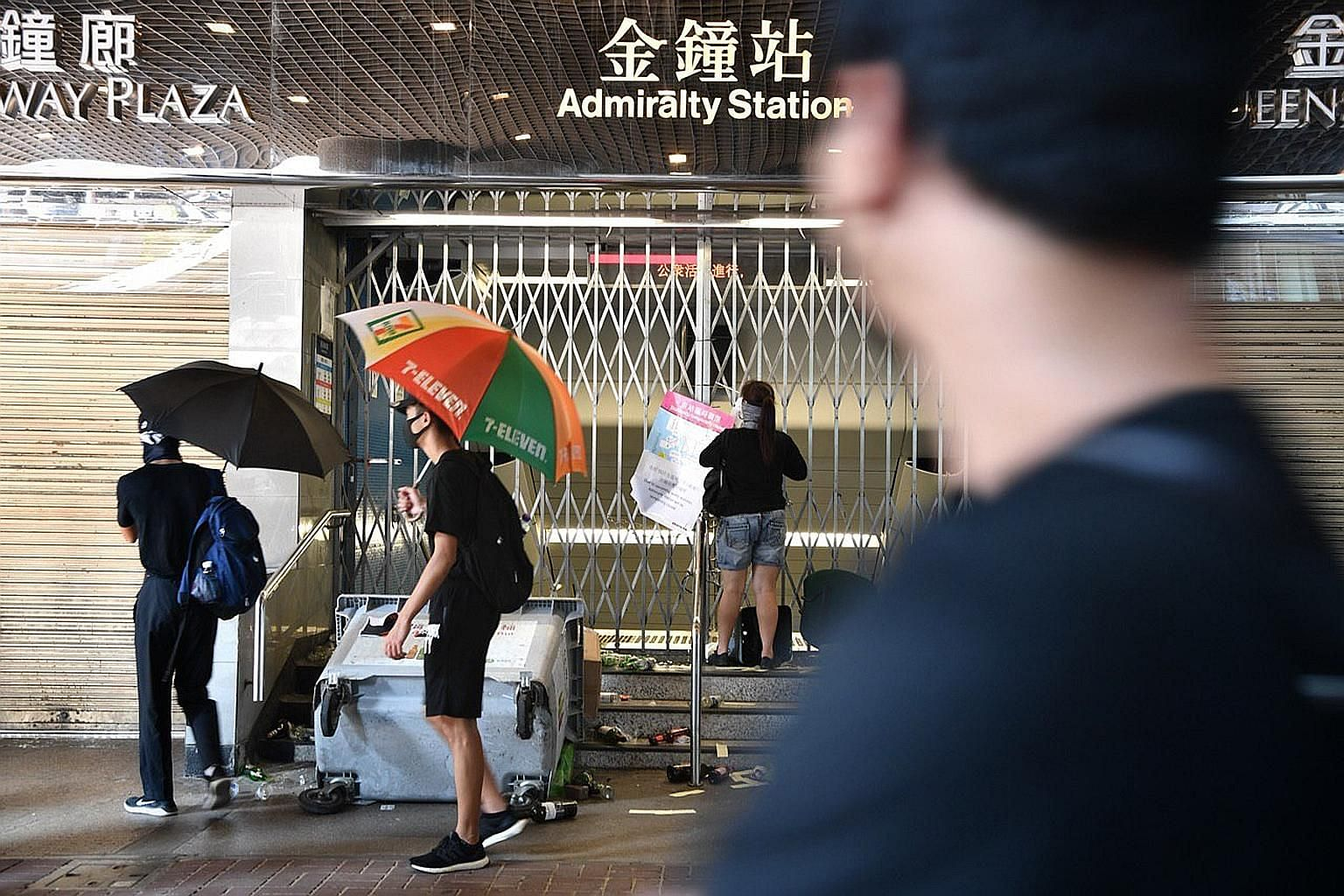 Above: Mr Mak Pui Tung says he is saddened that the protests have caused a divide between metro staff and commuters. Right: A protester securing the gates at Admiralty station with cable ties on Tuesday. The metro operator has been targeted by protes