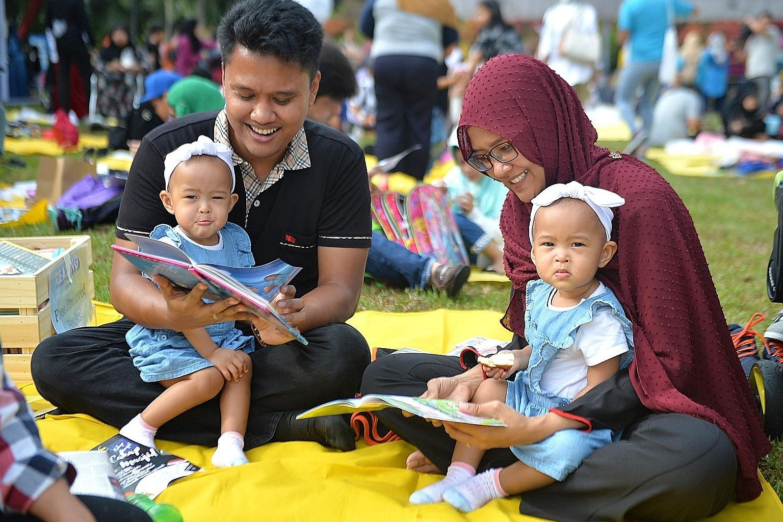 Civil servant Helmi Rosman and his wife Nurkamaliah Omar, both 31, reading with their one-year-old twin daughters Naura (left) and Husna. They were among 1,500 people who turned up for Reading @ The Gardens at Gardens by the Bay yesterday morning, as