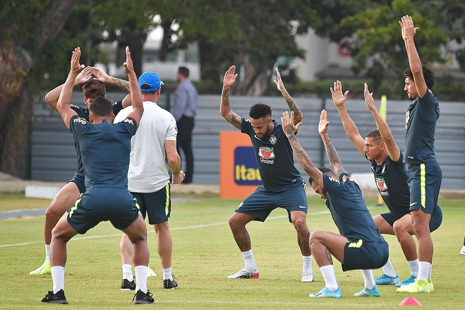 Above: Neymar and his Brazil teammates limbering up at Kallang Football Hub yesterday afternoon. Left: Forward Richarlison posing for a wefie with fans as he departs the team's hotel.