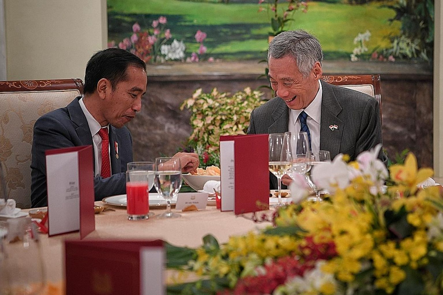 Indonesian President Joko Widodo and Prime Minister Lee Hsien Loong sharing a light moment over keropok and sambal at the start of their dinner yesterday at the Istana, during this year's Singapore-Indonesia Leaders' Retreat. ST PHOTO: MARK CHEONG