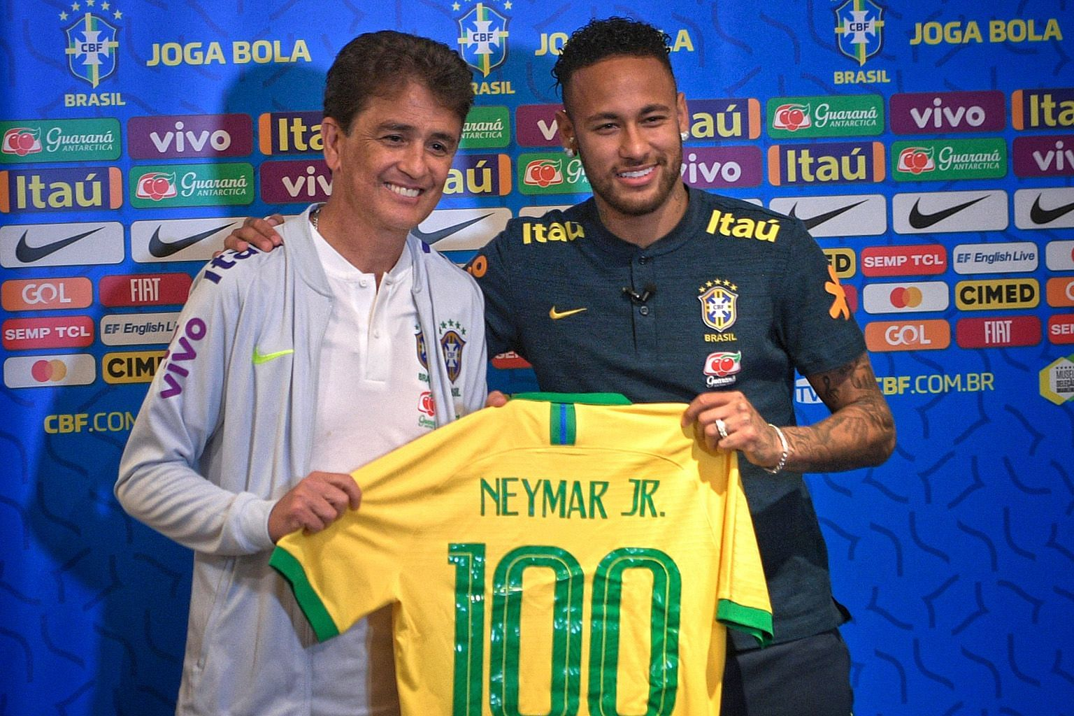 Former Brazil striker Bebeto handing talisman Neymar a jersey with the number 100 yesterday to commemorate the latter's 100th cap for Brazil in today's match against Senegal. The Selecao have drawn fans in Singapore including these flag-bearers at Ka