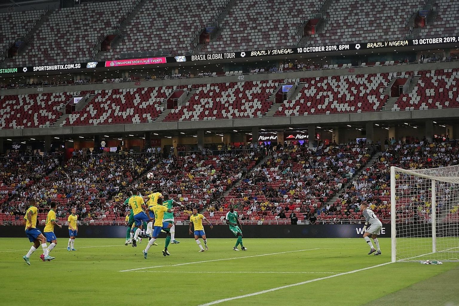 Above: A man resembling Liverpool forward Mohamed Salah posing for a photo during the game. ST PHOTO: JASON QUAH Left: The match was played in a half-empty National Stadium, with the two upper decks left unoccupied.