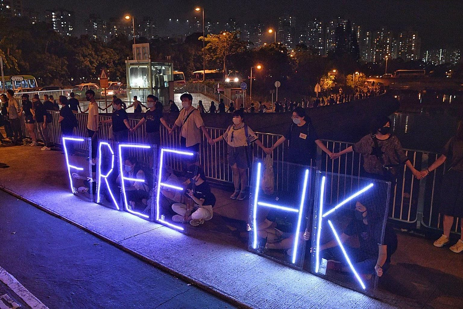 Protesters forming a human chain in Hong Kong's Tai Po District last night, as rallies continued.